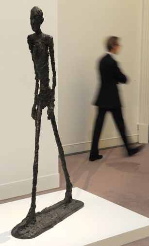 A man walks past a sculpture by Swiss artist Alberto Giacometti entitled 'L'Homme qui marche I' at Sotheby's auction house, in London, on January 12, 2010. Sotheby's unveiled on Tuesday three impressionist and modern art masterpieces, a painting by Klimt entitled 'Kirche in Cassone (Landschaft mit Zypressen)', which is expected to reach between GBP 12-18m (dollars 19-29m or euros 14-20m), a painting by French artist Paul Cezanne entitled 'Pichet et fruits sur une table', which is estimated to reach between GBP 10-15m GBP (dollars 16-24m or euros 11-16.7m) and a sculpture by Swiss artist Alberto Giacometti entitled 'L'Homme qui marche I' which is estimated to reach between GBP 12-18m (dollars 19-29m or euros 14-20m) when they are auctioned at the Evening Sale of Impressionist and Modern Art, on February 3, 2010, in London. AFP PHOTO/Carl de Souza